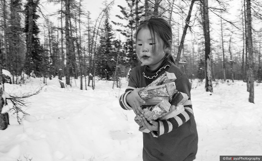 A girl, who glossed her lips, helped the family to collect woods. Winter is time to go to school for children